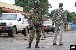 FILE - A Burundian soldier with his gun and rocket launcher guard a deserted street in Bujumbura, Burundi.
