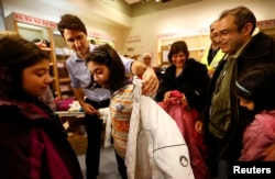 FILE - Canada's Prime Minister Justin Trudeau helps a young Syrian refugee try on a winter coat after she arrived with her family from Beirut at the Toronto Pearson International Airport in Mississauga, Ontario, Canada, Dec. 11, 2015.
