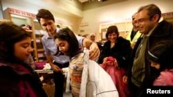 El primer ministro de Canadá, Justin Trudeau, ayuda a una joven refugiada siria a probarse un abrigo. La niña llegó con su familia procedente de Beirut, con el primer grupo de refugiados sirios que llegó a Canadá en un avión militar, en 2015.