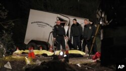 Investigators examine body bags of victims near the scene where at least eight people were killed and 38 people were injured after a tour bus carrying a group from Tijuana, Mexico crashed with two other vehicles near Yucaipa, California, February 3, 2013.