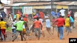 Des manifestants s'enfuient devant la police antiémeute dans un quartier de Conakry, le 21 novembre 2017.