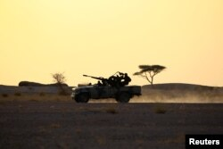 FILE - The Polisario Front soldiers drive a pick-up truck mounted with an anti-aircraft weapon during sunset in Bir Lahlou, Western Sahara, Sept. 9, 2016.