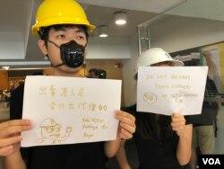 香港中文大學學生在善衡書院飯堂入口手持標語,呼籲師生杯葛飯堂經營者美心集團。(美國之音湯惠芸攝)