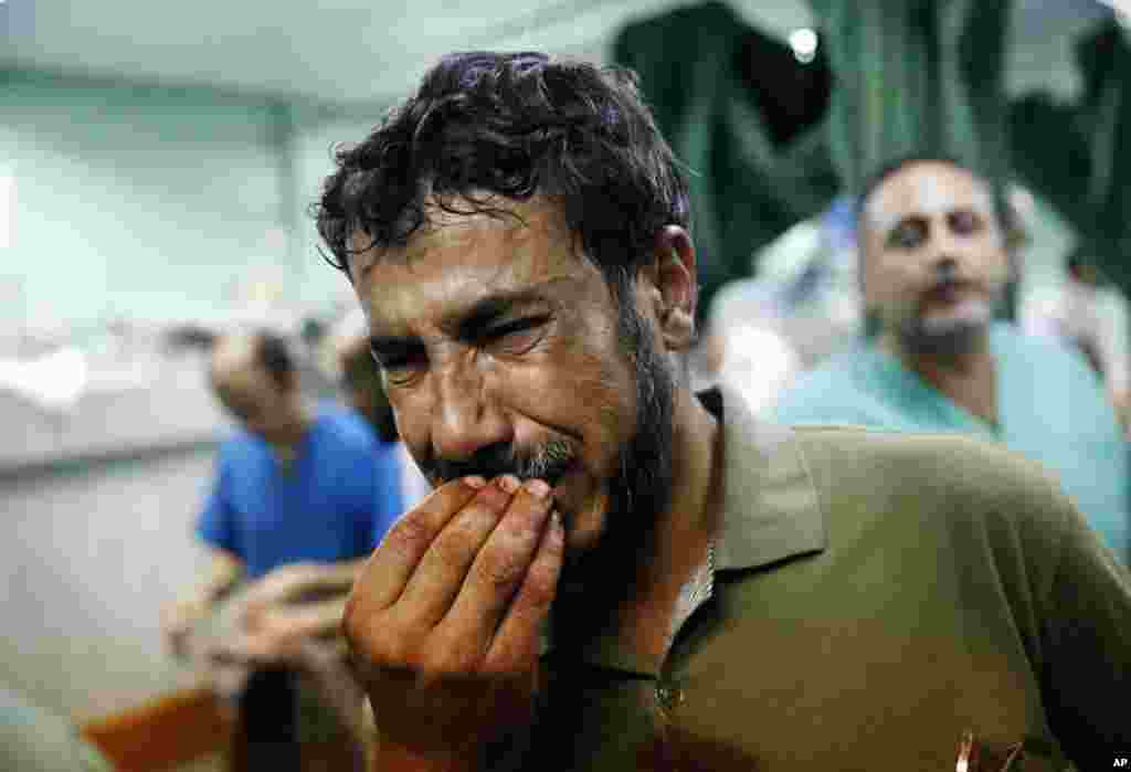 A Palestinian man cries after bringing a child, wounded in an Israeli strike on a compound housing a U.N. school in Beit Hanoun, in the northern Gaza Strip, to the emergency room of the Kamal Adwan hospital in Beit Lahiya.