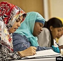Zaytuna College berharap para mahasiswi ini kelak menjadi cendekiawan-cendekiawan Muslim Amerika. (Dari kiri ke kanan) Linda Amrou dan Amirah Al-Gaheem sedang mencatat pelajaran Bahasa Arab di dalam kelas.