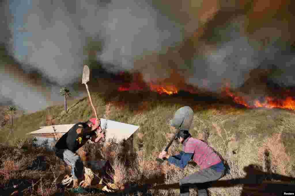 Residents work to prevent a wildfire from spreading to their homes in Vina del Mar, Chile, March 12, 2017.