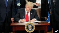 Donald Trump signe un décret lançant le projet de construction d'un mur à la frontière entre les Etats-Unis et le Mexique, le 25 janvier 2017.
