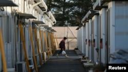 一位女士走过临时栖身所,从福岛县田村市转移出来的居民在这里暂时落脚。(2014年4月1日)