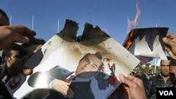 Para demonstran membakar foto Presiden Tunisia Zine el-Abidine Ben Ali di Tunis, 24 Januari 2011.
