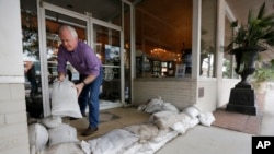 Scott Youngblood moves sandbags into place in front of the furniture store Augustus & Carolina in Georgetown, S.C., Oct. 6, 2015.