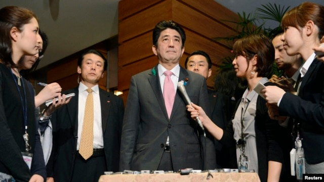 Japan's Prime Minister Shinzo Abe (C) speaks to media after a meeting with cabinet ministers at his official residence in Tokyo, in this photo taken by Kyodo, April 12, 2013.