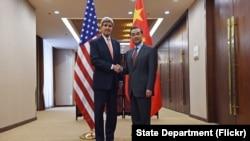 美国国务卿克里(左)在北京与中国外长王毅会谈前握手.(2016年1月27日)