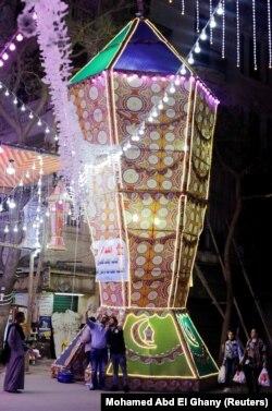 """Orang-orang mengambil foto di samping lentera Ramadhan tradisional yang disebut """"fanous"""" menjelang bulan suci Ramadhan, di tengah pandemi COVID-19 di Kairo, Mesir, 8 April 2021. (Foto: REUTERS/Mohamed Abd El Ghany)"""