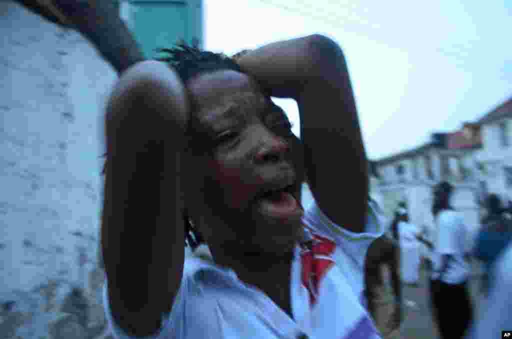 ຜູ້ສະໜັບສະໜຸນຜູ້ນຶ່ງຕໍ່ພັກປະຊາຊົນ Sierra Leone ຫລື SLPP ທີ່ເປັນພັກຝ່າຍຄ້ານນັ້ນ ຮ້ອງໄຫ້ ຢູ່ນອກຫ້ອງການຂອງທ່ານ Julius Maada Bio ຜູ້ສະໝັກເລືອກ ຕັ້ງຈາກພັກ SLPP ລຸນຫລັງມີການປະກາດວ່າ ທ່ານເສຍໄຊໃນການເລືອກຕັ້ງແລ້ວ, ຢູ່ໃນນະຄອນ Freetown ໃນວັນສຸກ ທີ 23 ພະຈິກ 2012. (AP Photo/Tommy Trenchard)