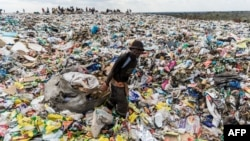 FILE - A recycler drags a huge bag of paper sorted for recycling past a heap of non-recyclable material at Richmond sanitary landfill site on 2 June 2018 in the industrial city of Bulawayo.