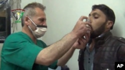 FILE - This video image from an anti-Bashar Assad activist group shows a Syrian being treated with an inhaler in Kfar Zeita, north of Damascus, after what witnesses said was a chlorine gas attack, April 18, 2014.