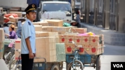 Nhân viên hải quan Việt Nam đứng cạnh hàng hóa của Trung Quốc tại cửa khẩu Tân Thanh (Ảnh: Daniel Schearf/VOA).