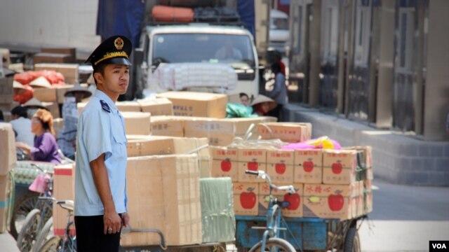 Nhân viên hải quan Việt Nam bênh cạnh hàng hóa được mua bán tại cửa khẩu Tân Thanh, Lạng Sơn. (D. Schearf/VOA)