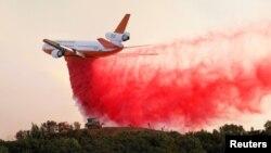 ایک جہاز جنگل میں لگی آگ پر آگ بجھانے والے کیمیکل کی بارش کر رہا ہے۔
