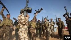 Para pejuang Irak dari unit mobilisasi Muslim Syiah Al-Abbas menyandang senjata di desa Nukhayb, provinsi Anbar (19/5). (AFP/Mohammed Sawaf)