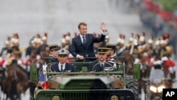 Presiden Perancis baru Emmanuel Macron di atas mobil militer di Champs Elysees menuju Arc de Triomphe di Paris, 14 Mei 2017.