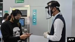 Seorang petugas MRT yang memakai pelindung wajah membantu seorang penumpang yang memakai masker, di Jakarta (foto: dok).