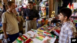FILE - A bazaar vendor selling patriotic and pro-independence ware talks with a customer in Irbil, Iraq, Aug. 24, 2017. Despite calls from Baghdad and the United States to postpone the vote, Iraq's semiautonomous Kurdish region is pressing ahead with plans to hold a referendum on independence Sept. 25.
