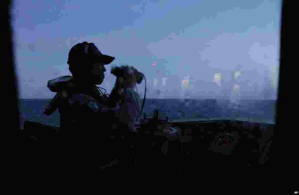 A crew member keeps an eye on the horizon at dawn during exercises off the southern city of Kaohsiung, Taiwan, May 16, 2013.