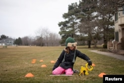 Molly Maguire, 8, measures the distance between cones during a math exercise learning how to calculate the area of different shapes in her front yard as schools are closed to combat the spread of coronavirus disease (COVID-19) in Salem Township