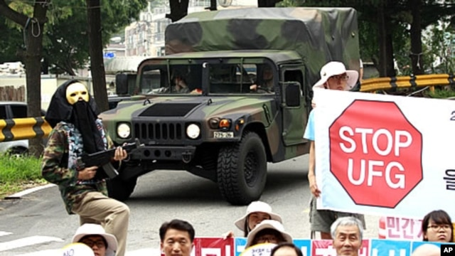 U.S. Army vehicle passes by South Korean protesters at a rally denouncing a South Korea-U.S. Combined Forces Command military exercise, in Seongnam, south of Seoul, South Korea, August 16, 2011