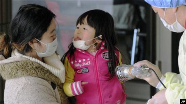 Mother and daughter receive radiation exposure scanning in Fukushima, northern Japan Friday, one week after a massive earthquake and tsunami, March 18, 2011
