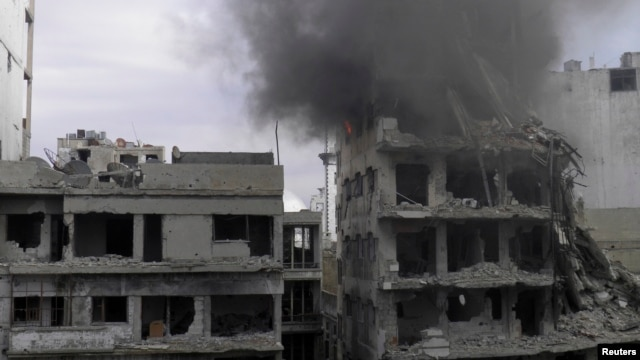 Smoke rises from a building after it was hit by what activists said was shelling by forces loyal to Syria's President Bashar al-Assad at the besieged area of Homs, Jan. 9, 2014.
