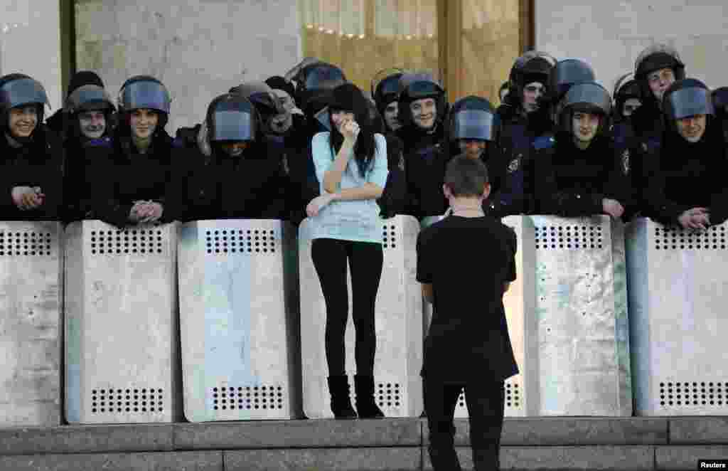 A man takes photos of his girlfriend next to Ukrainian riot police guarding the regional administration building following a pro-Russian rally in Donetsk, March 23, 2014.