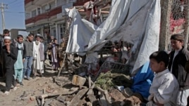 Afghans look at wreckage after a roadside bomb explosion went off on the outskirts of Kabul, Afghanistan, Sunday, Oct. 27, 2013.