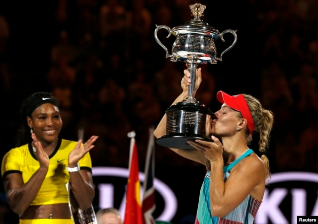 Germany's Angelique Kerber kisses the trophy as Serena Williams of the U.S. claps after Kerber won their final match at the Australian Open tennis tournament at Melbourne Park, Australia, Jan. 30, 2016.