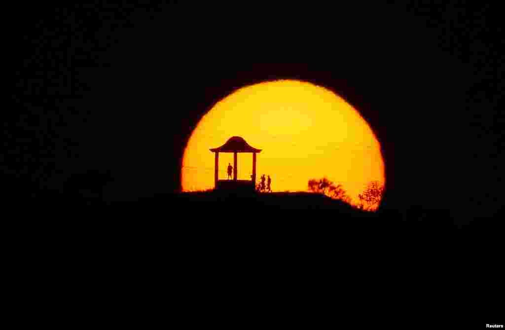 People are silhouetted against the setting sun at 'El Mirador de la Alemana' (The viewpoint of the German), as the summer's second heatwave hits Spain, in Malaga, southern Spain July 24, 2019.