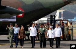FILE - Indonesia President Joko Widodo, center, talks with Indonesian Army Chief of Staff Gen. Gatot Nurmantyo, during inspection of aids for Rohingya before its departure at Halim Perdanakusuma air base in Jakarta, Sept. 13, 2017.