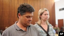 FILE - Game farmer Dawie Groenewald, left, and his wife, Sariette, right, appear in court in Musina, South Africa, Wednesday, Sept 22, 2010.