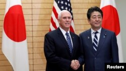 U.S. Vice President Mike Pence shakes hands with Japanese Prime Minister Shinzo Abe at Abe's official residence in Tokyo, Japan.