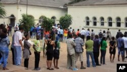 FILE - Voters line up to cast their votes at a polling station, in Maputo, Mozambique, Oct. 15, 2014.