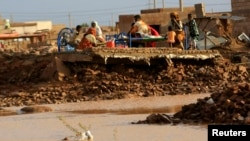Family members rest in the remains of their house destroyed by floods caused by heavy rains in Khartoum Aug. 6, 2013.