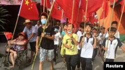 Villagers including schoolchildren take part in a protest march, demanding the release of their village chief Lin Zulian, in Wukan, in China's Guangdong province, June 21, 2016.