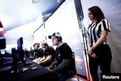 "A referee watches over competitors playing ""Call of Duty: Infinite Warfare"" on the Playstation 4, during the Cineplex WorldGaming Canadian Championship Series, an esports video game tournament, n Toronto, Ontario, March 26, 2017."