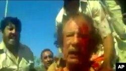 ຮູບຈາກມືກ້ອງວີດີໂອສະມັກຫຼິ້ນທີ່ພິມເຜີຍແຜ່ໂດຍສື່ສັງຄົມ ແລະອົງການຂ່າວຣອຍເຕີ້ໄດ້ຮັບມາສະແດງໃຫ້ເຫັນ ວ່າ ທ່ານມວມມາກາດດາຟີ ມີເລືອດອາບໂຕ ຫຼັງຈາກນັກພວກນັກລົບ ຂອງລັດຖະບານຊົ່ວຄາວລີເບຍຈັບໄດ້ທີ່ ເມືອງ Sirte (21 ຕຸລາ 2011)