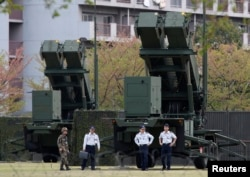 Binh sĩ Nhật đứng cạnh bệ phóng tên lửa đánh chặn Patriot (PAC-3) tại Bộ Quốc phòng ở Tokyo. .