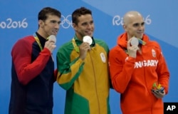 Men's 100-meter butterfly silver medalists, from left, United States' Michael Phelps, South Africa's Chad Le Clos and Hungary's Laszlo Cseh hold up their medals at the medal ceremony during swimming competitions at the 2016 Summer Olympics, Friday, Aug. 12, 2016, in Rio de Janeiro, Brazil.