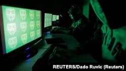 """Des utilisateurs d'ordinateurs devant un écran montrant le mot """"cyber"""" en code binaire, dans cette photo d'illustration prise le 27 décembre 2014."""