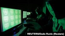 黑客坐在电脑前进行网络攻击模拟图