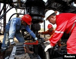 Men work at an oil pump in Lagunillas, Ciudad Ojeda, in the state of Zulia, Venezuela, March 20, 2015.