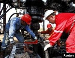 Men work at an oil pump in Lagunillas, Ciudad Ojeda, in the state of Zulia, Venezuela, March 20, 2015.